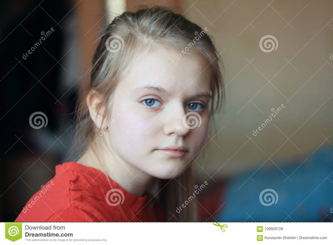 portrait of a blonde hair blue eyes girl teenager at home stock