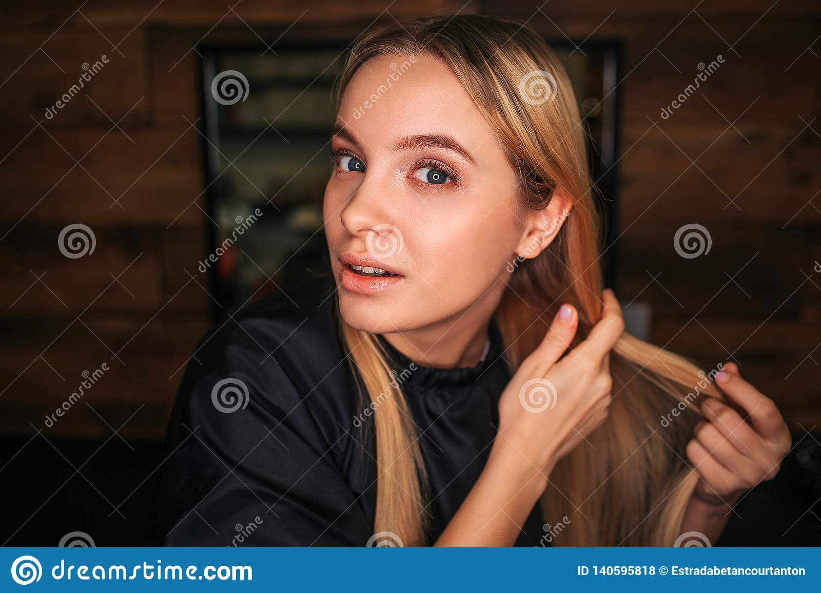Portrait of blonde young woman with black salon cape looking at camera while waiting for a hairdresser on salon
