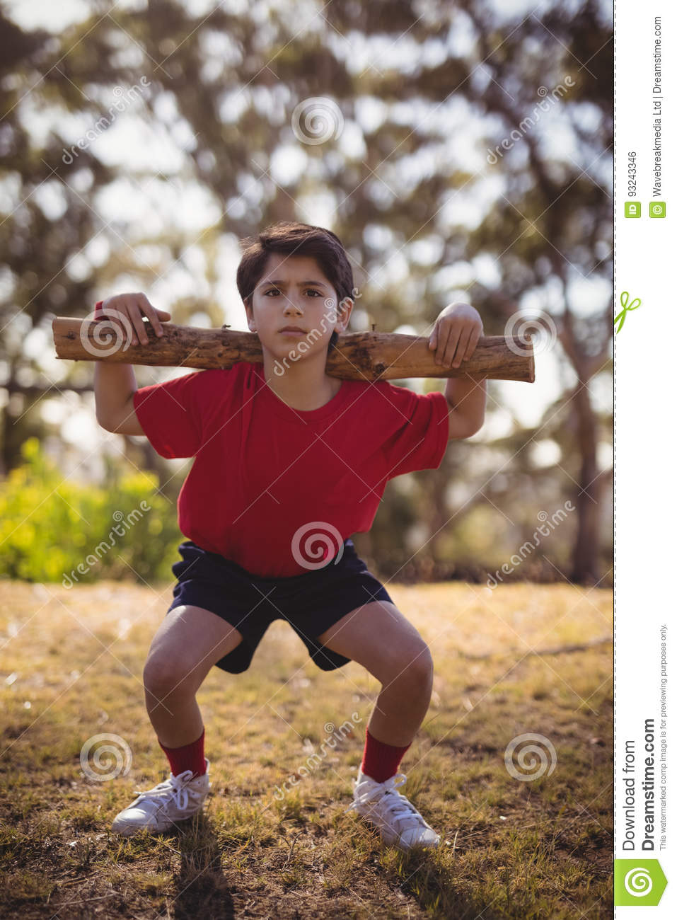 Portrait boy exercising with log during obstacle course