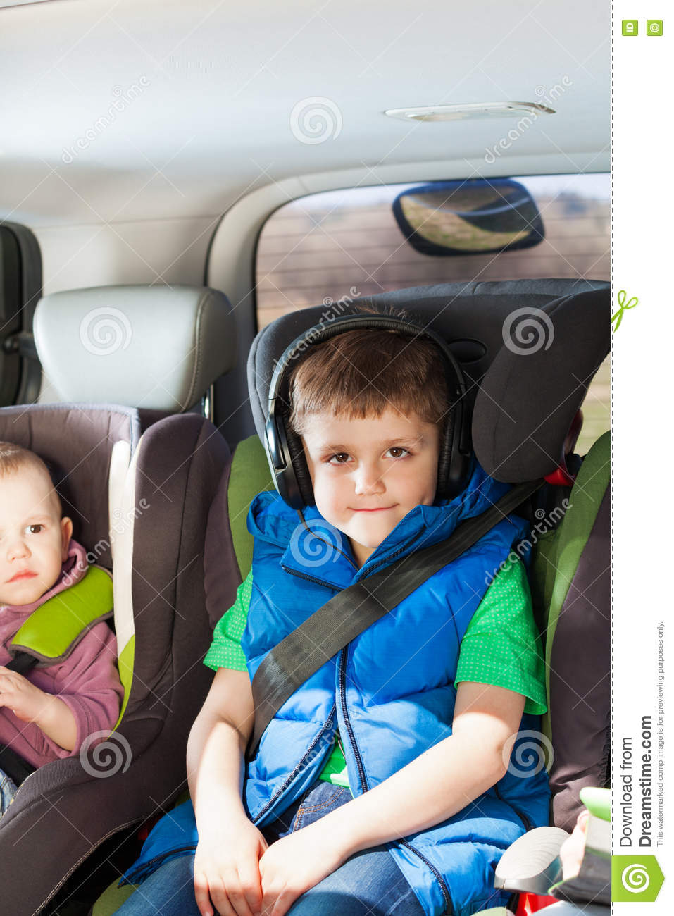 Portrait Of Five Years Old Boy Listening To Music In The Headphones Sitting Child Safety Seats