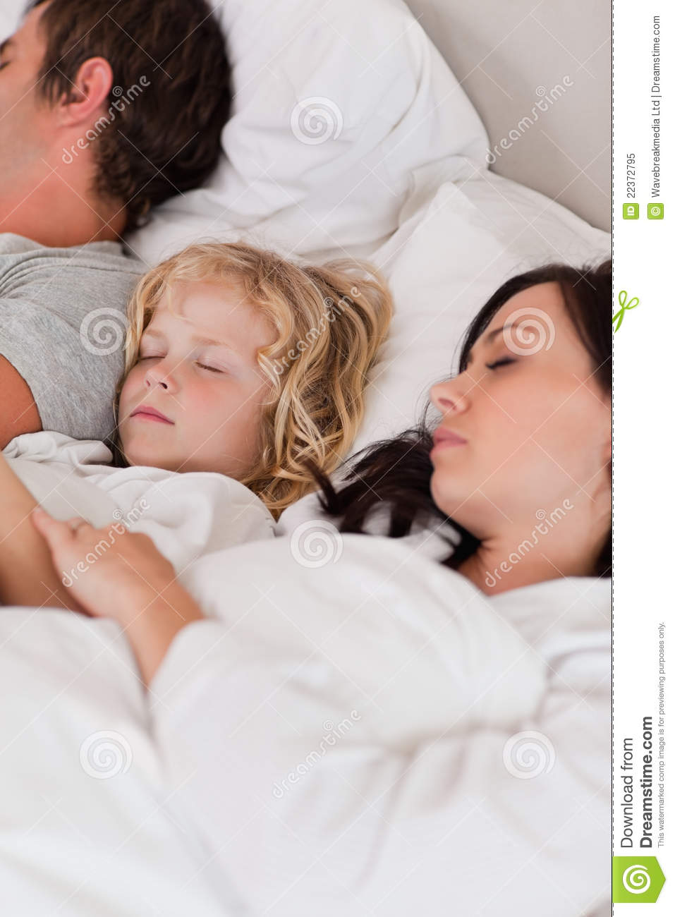 Baby Sleeping In Bedroom With Parents: Portrait Of A Boy Sleeping Between His Parents Royalty