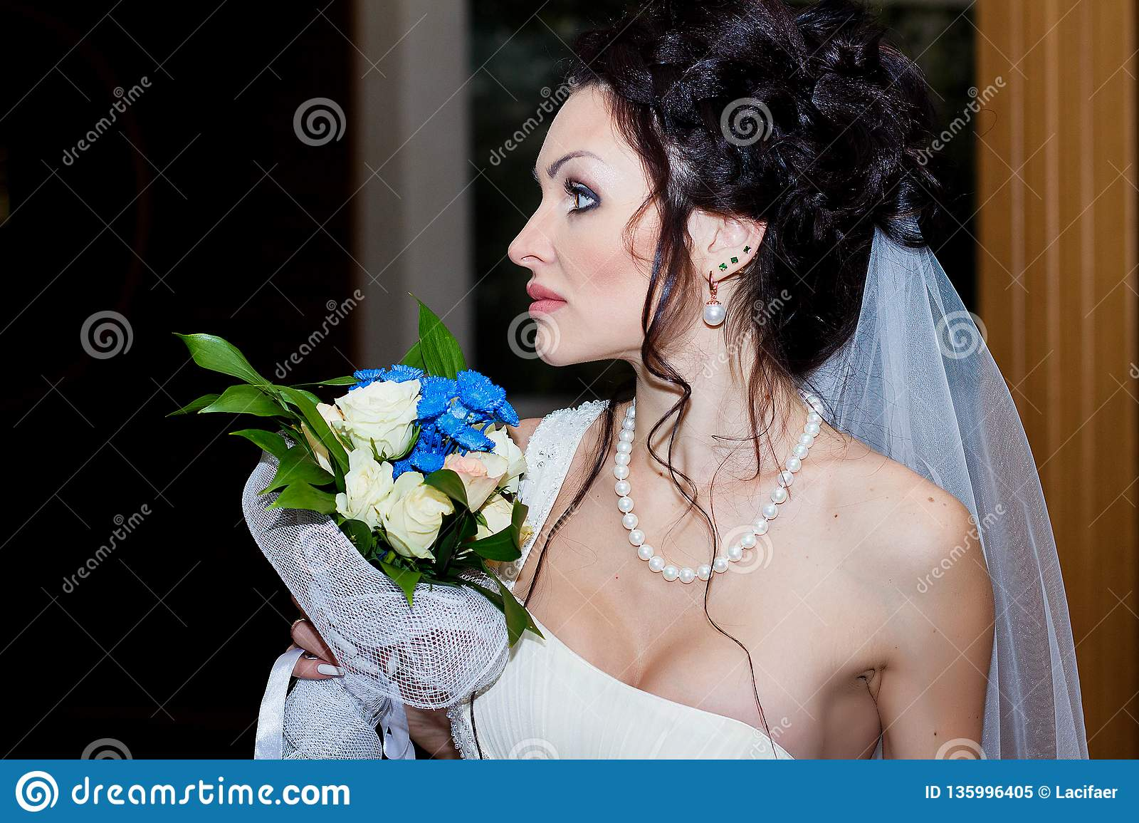 Portrait of the bride close-up with wedding bouquet. Indoor, Studio, interior