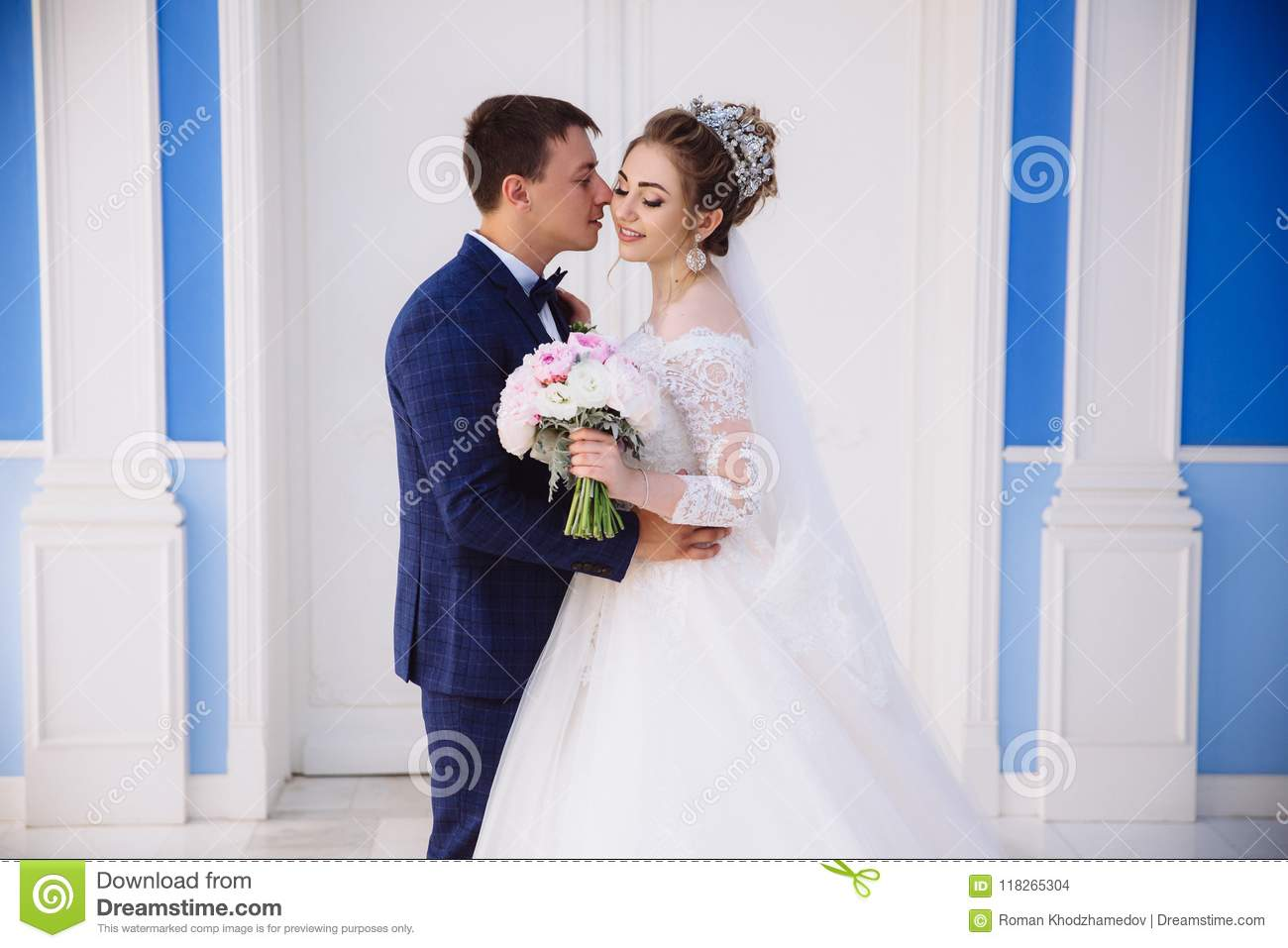 A portrait of the bride and groom who will soon become husband and wife. A man in a stylish suit hugs the girl at the