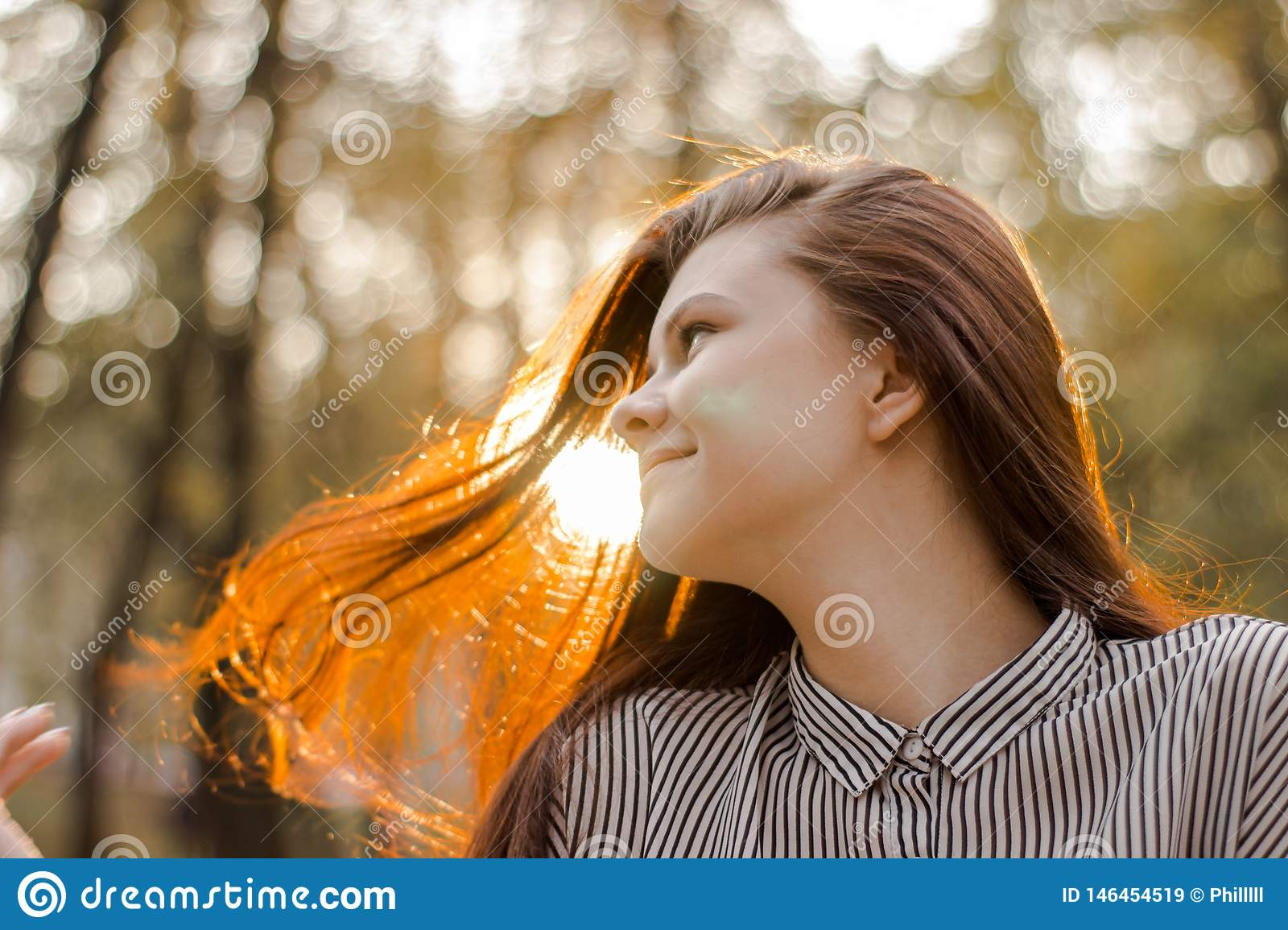 Portrait of a brown-haired girl whose sunset sunlight shimmers in her hair