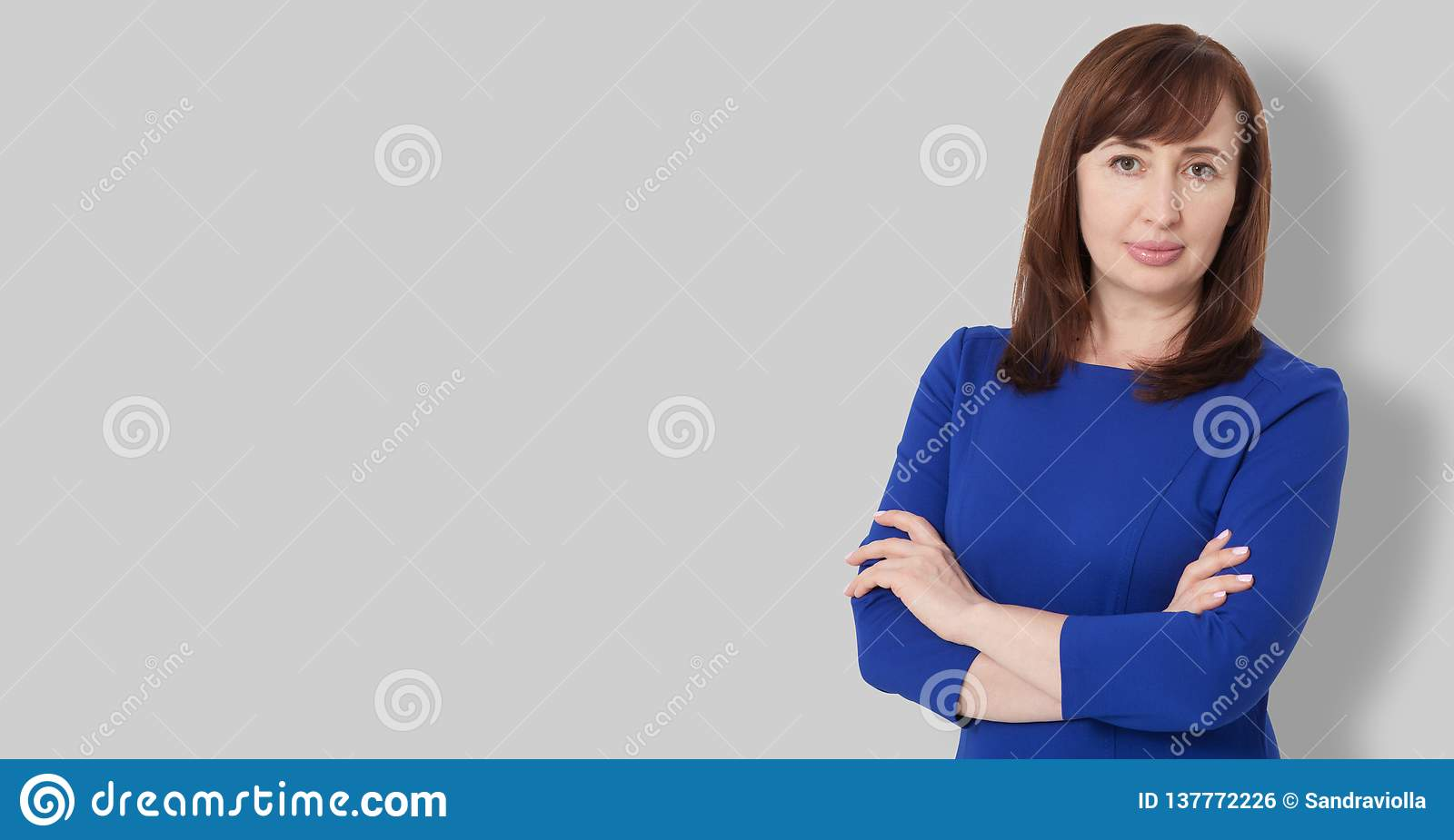 Portrait of brunette serious middle age boss woman in business dress isolated on gray background. Crossed arms on chest. Copy