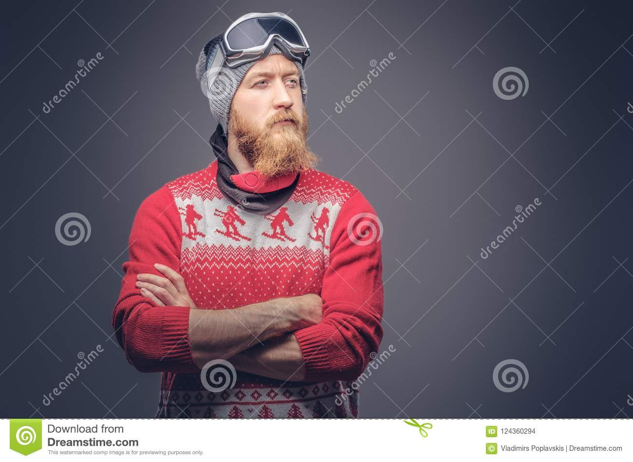 Portrait of a brutal redhead bearded male in a winter hat with protective glasses dressed in a red sweater, posing with