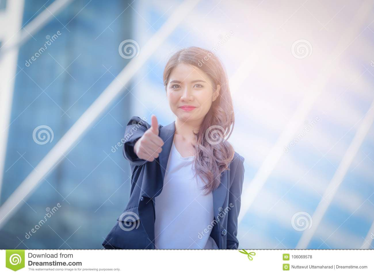 Portrait of business woman smiling and shows thumbs up on blurred city background. Business success concept.