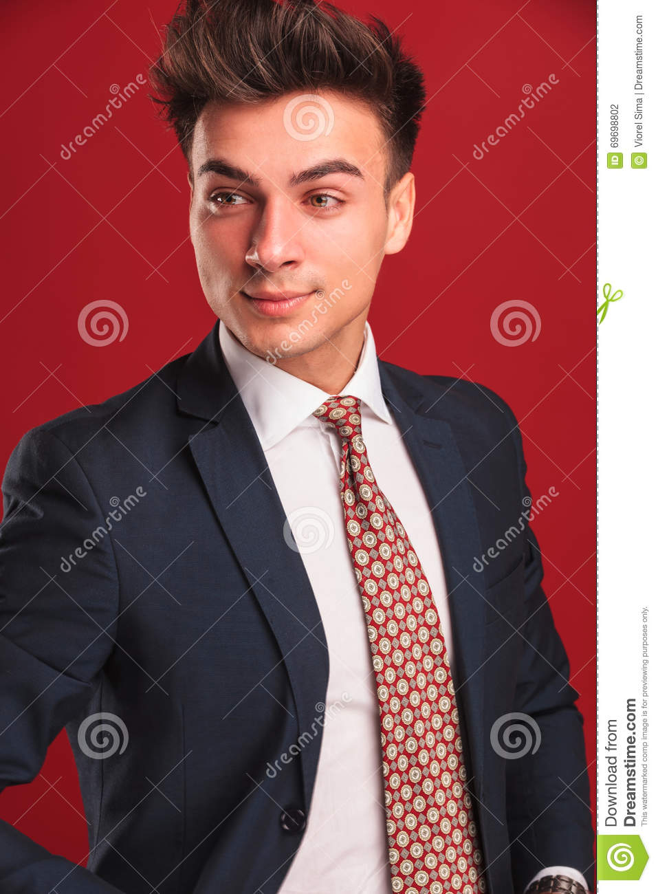3853227d0fca Closeup portrait of attractive young businessman in black suit with red tie,  with open jacket, posing in red studio background while looking away from  the ...