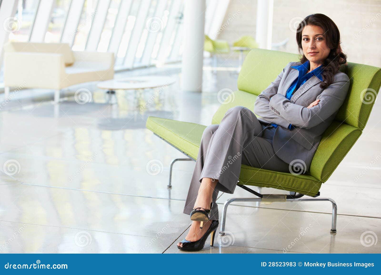Portrait of businesswoman sitting on sofa in modern office for Sofa 8 personen