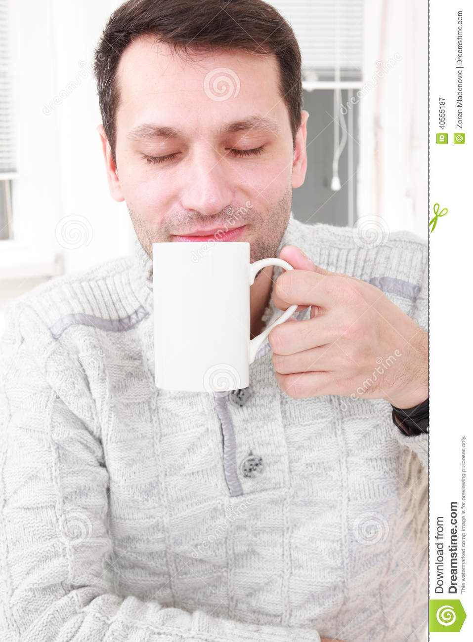 Portrait of a calm man having a coffee in his living room