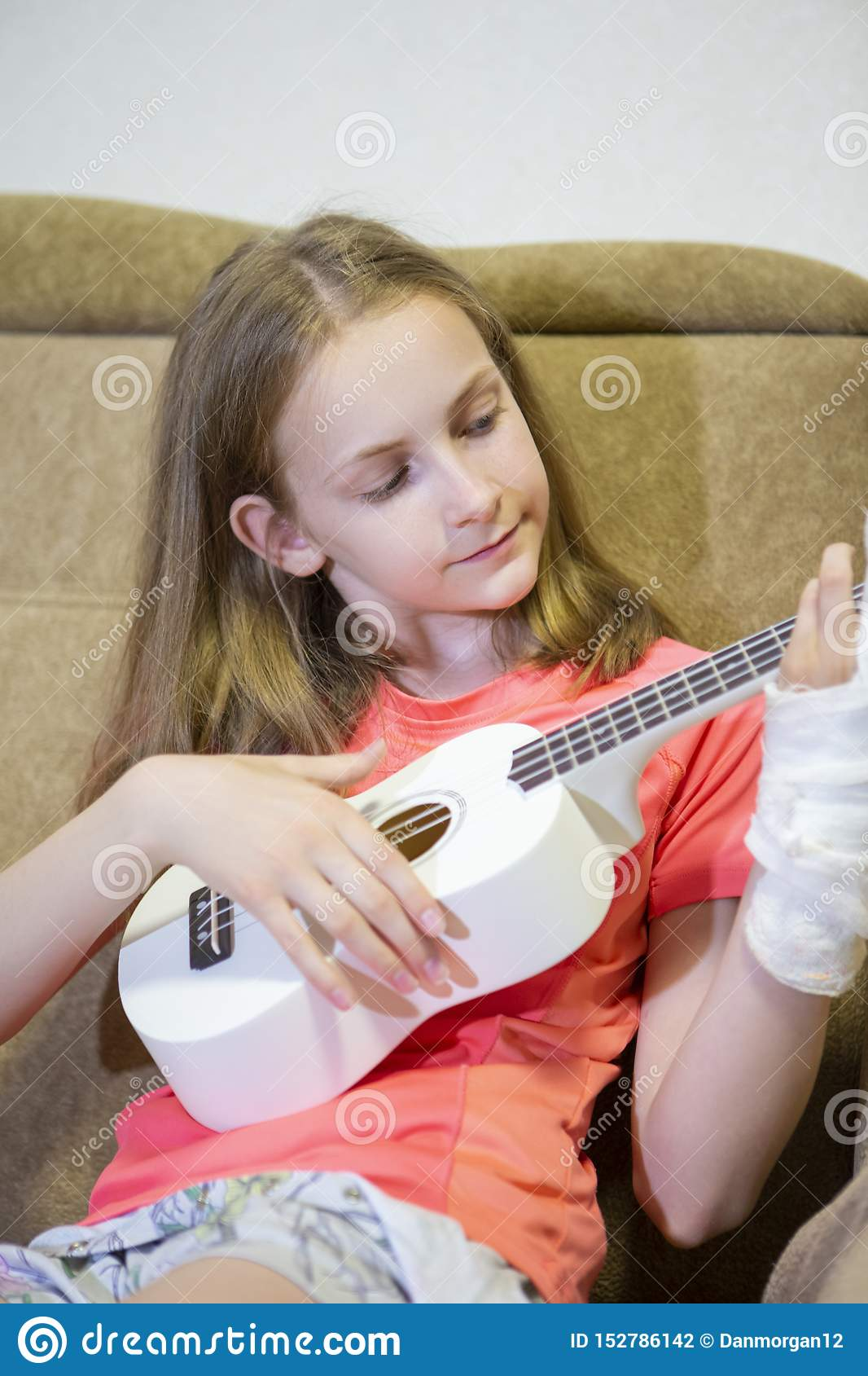 Portrait of Caucasian Girl With Injured Hand In Plaster Playing hawaiian Guitar Indoors