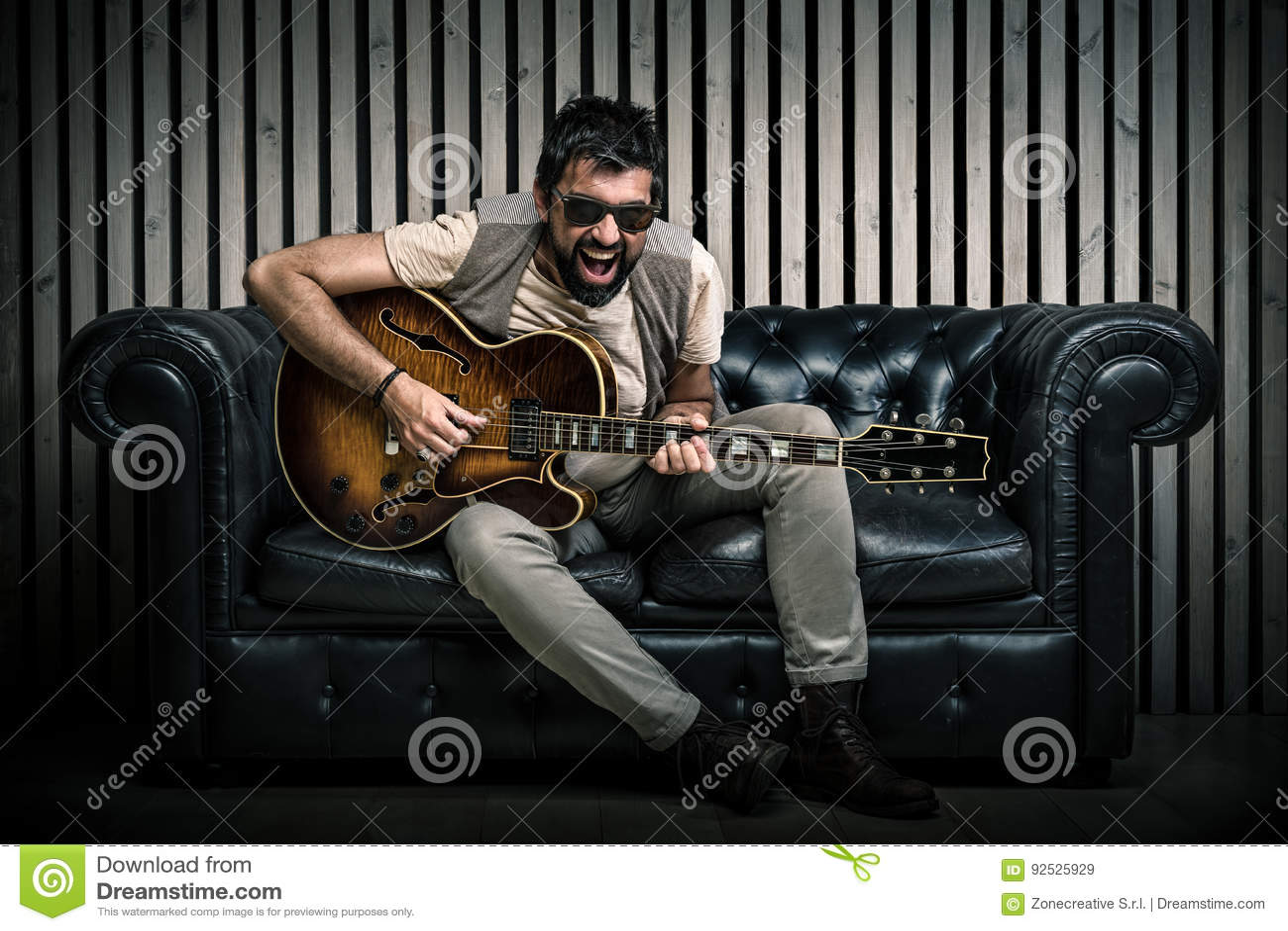 Portrait caucasien adulte de guitariste jouant la guitare électrique se reposant sur le sofa de vintage Concept de chanteur de mu