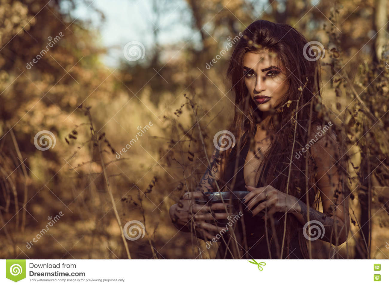 Portrait of charming dangerous young witch holding a pot with magic potion in the woods and looking straight with penetrating gaze