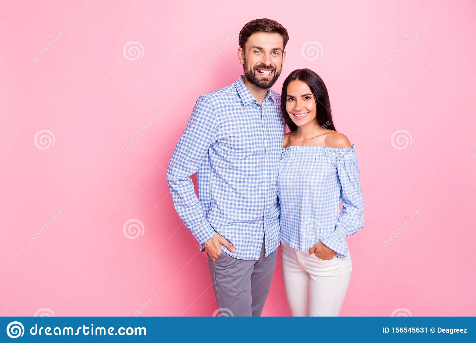 Portrait of charming sweethearts looking at camera with toothy smile isolated over pink background