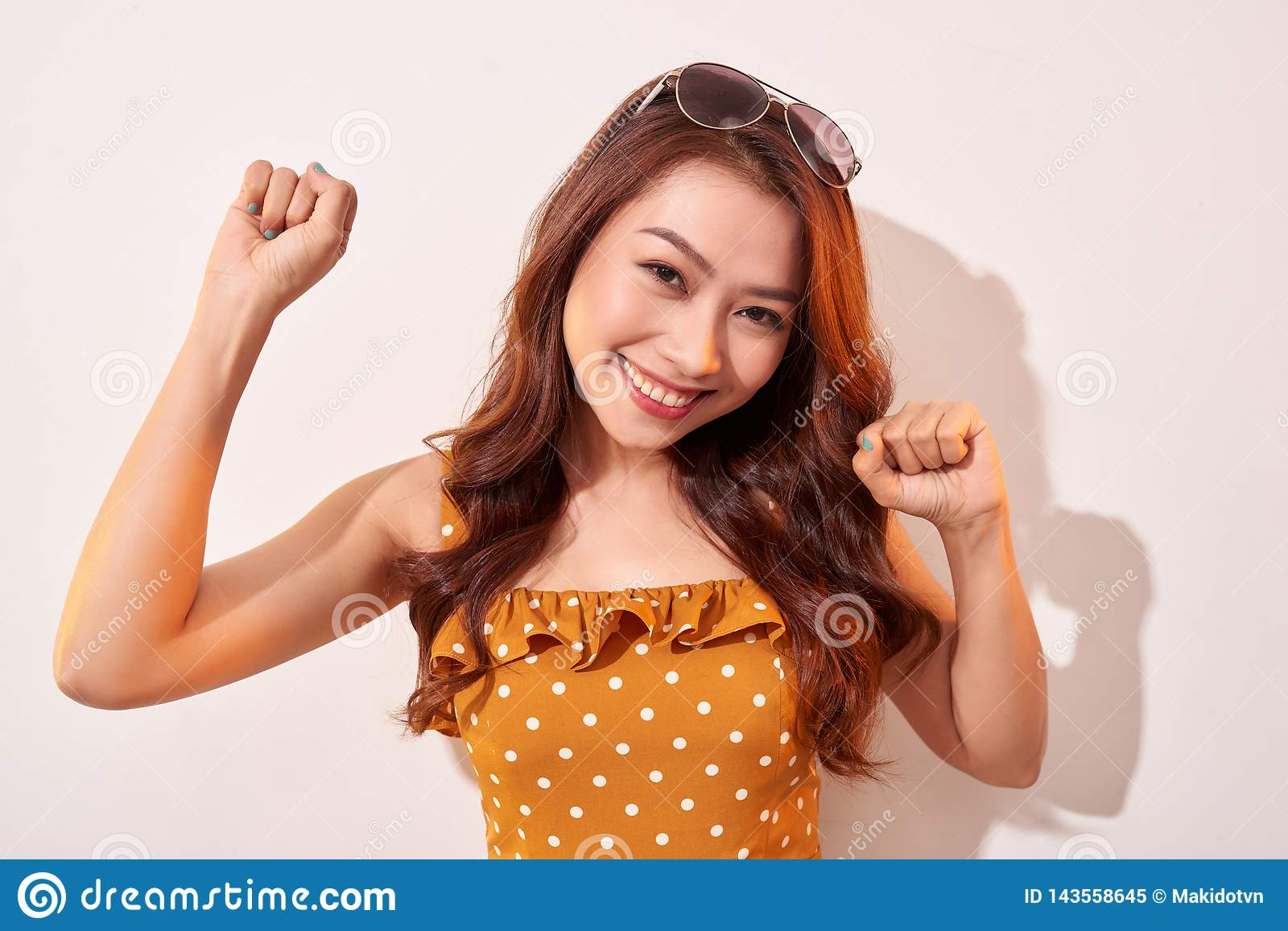 Portrait of cheerful fashion girl going crazy in a orange polka dots dress.
