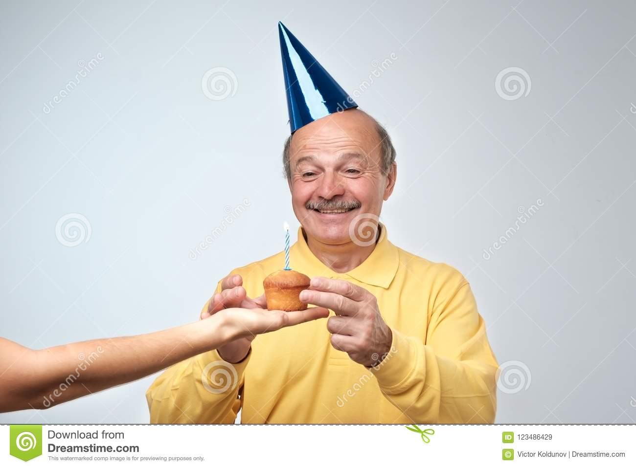 Portrait Of Cheerful Good Looking Birthday Guy With In Funny Cao His Friend Giving Him Cupcake He Is Smiling Broadly Happy Surprise Party