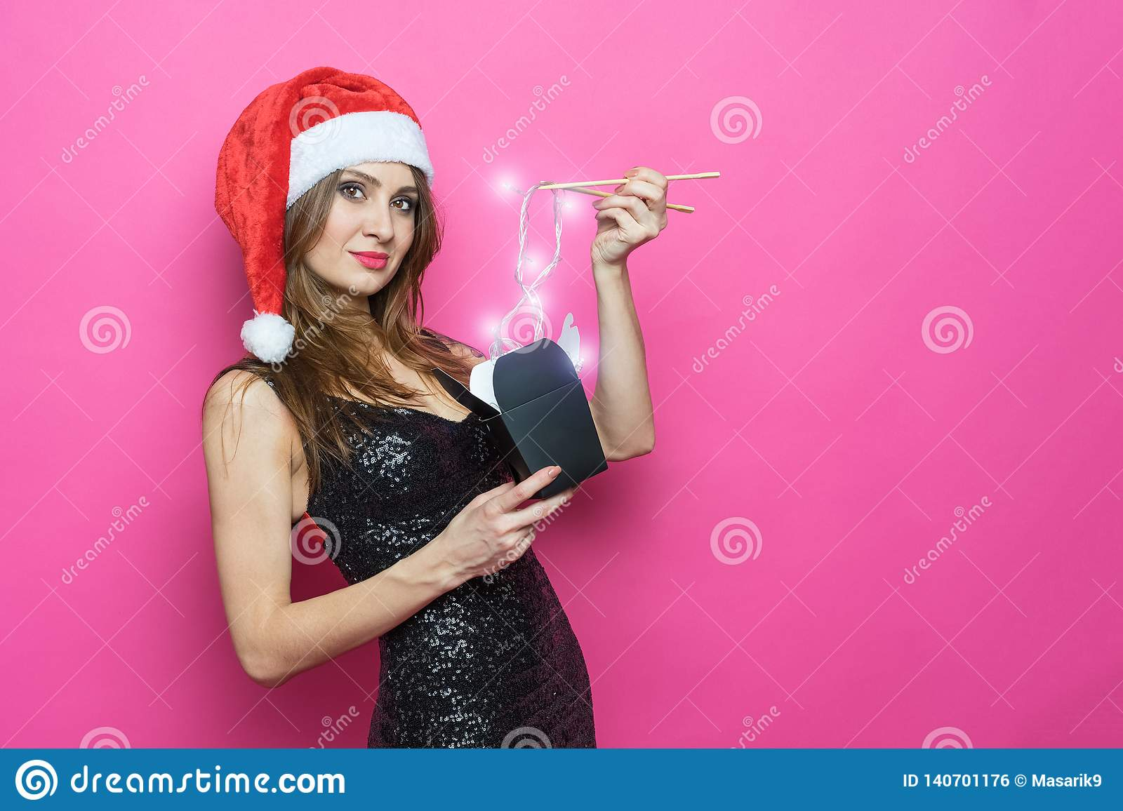 Portrait of a cheerful laughing brunette woman in christmas hat and exquisite black dress holds in her hand a paper box for instan
