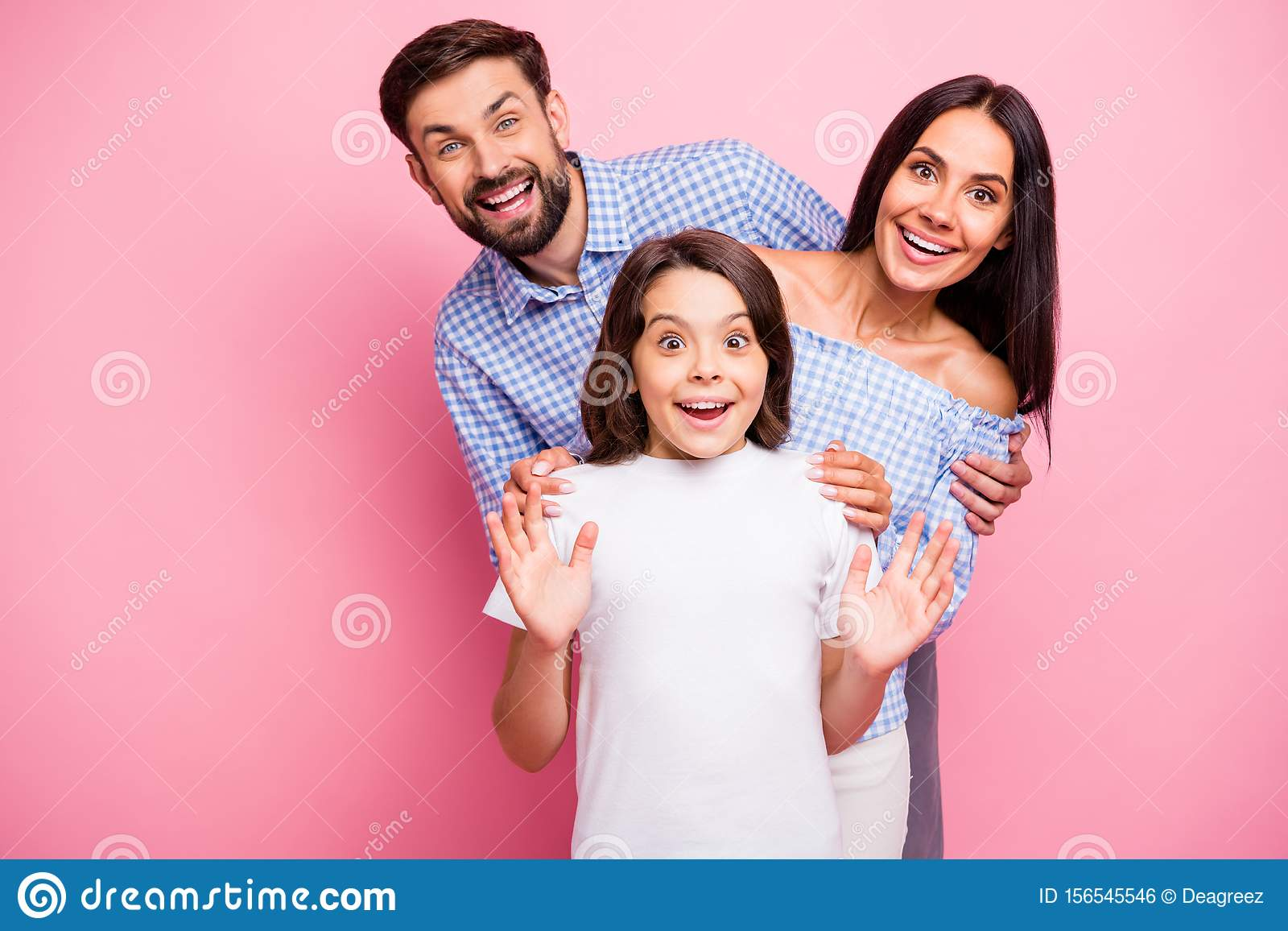 Portrait of cheerful people screaming wow omg wearing checkered top white t-shirt isolated over pink background