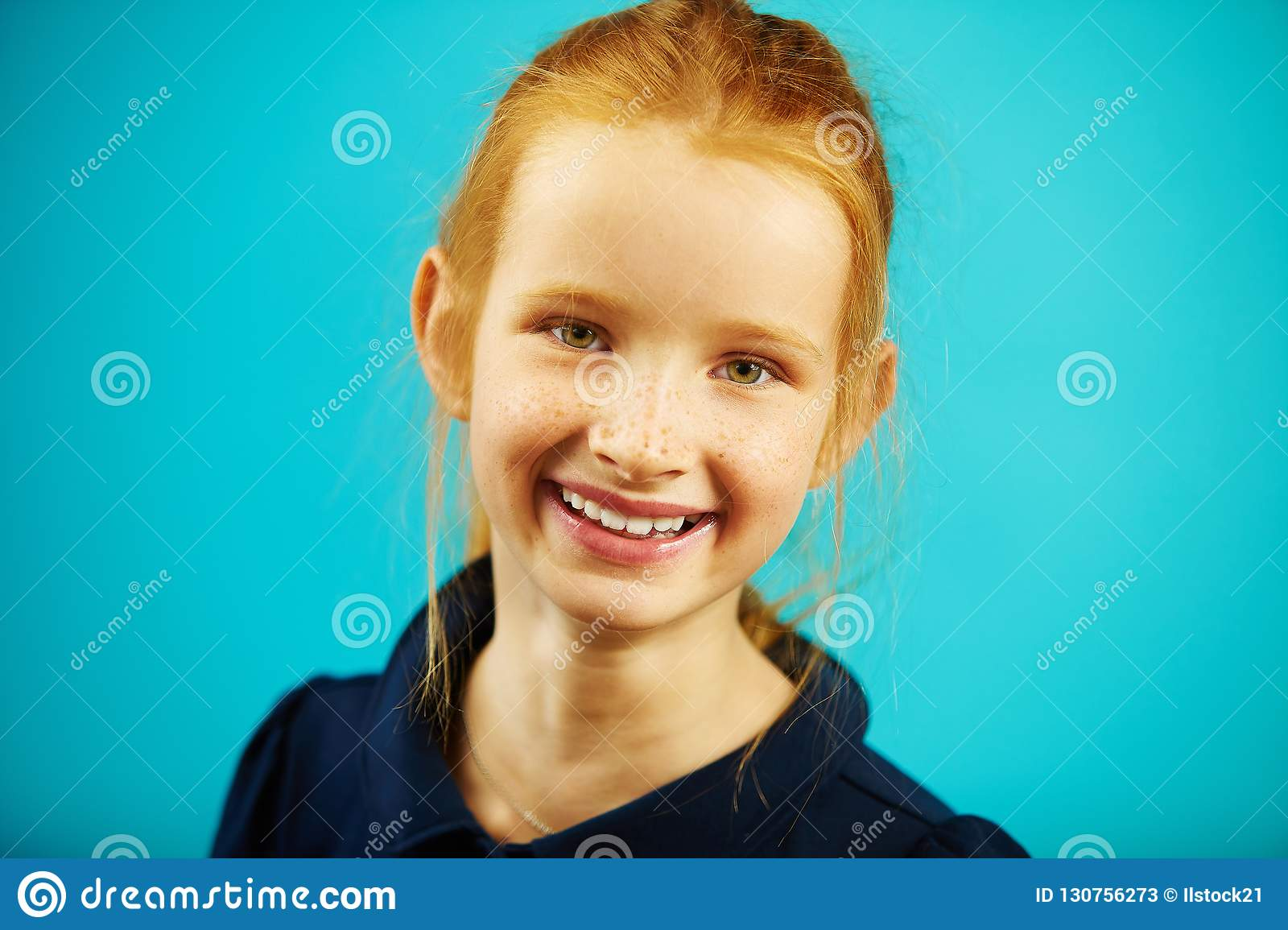 Portrait of cheerful redheaded school girl of seven years old on blue isolated background. Joyful child with genuine