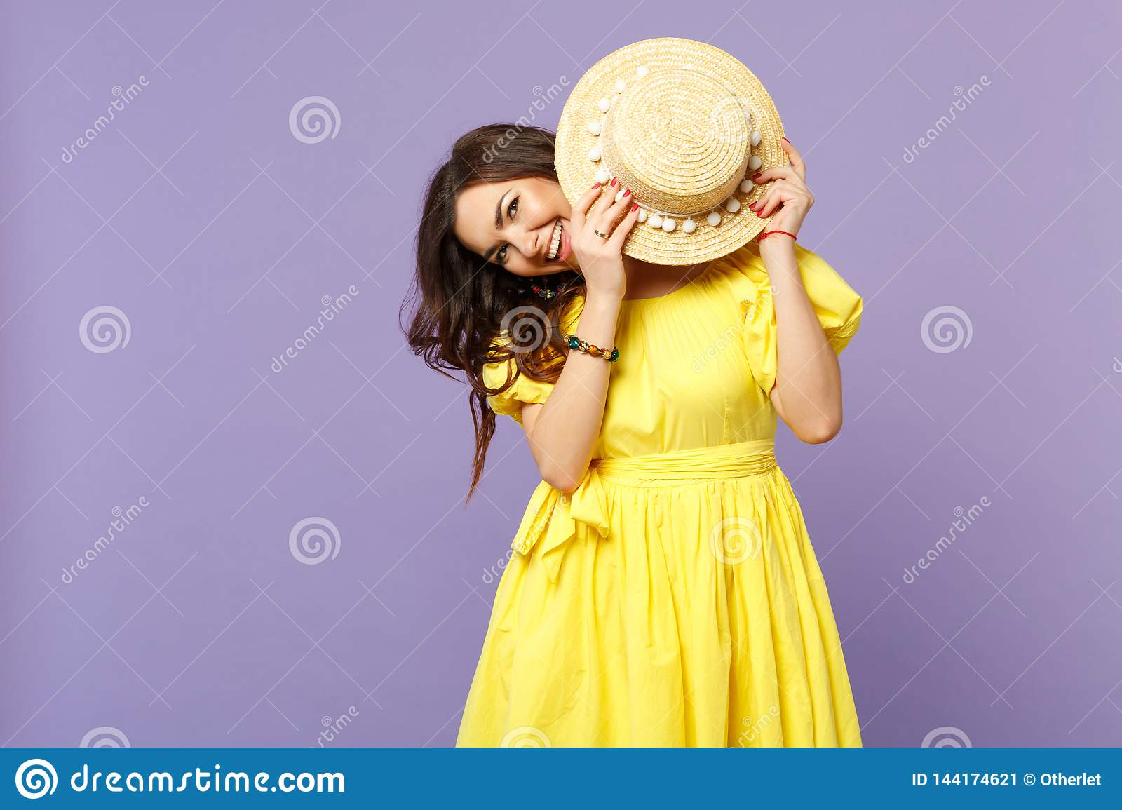 Portrait of cheerful smiling young woman in yellow dress covering face with summer hat  on pastel violet