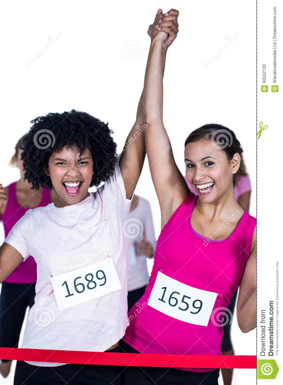 Portrait of cheerful winner athletes crossing finish line with arms raised