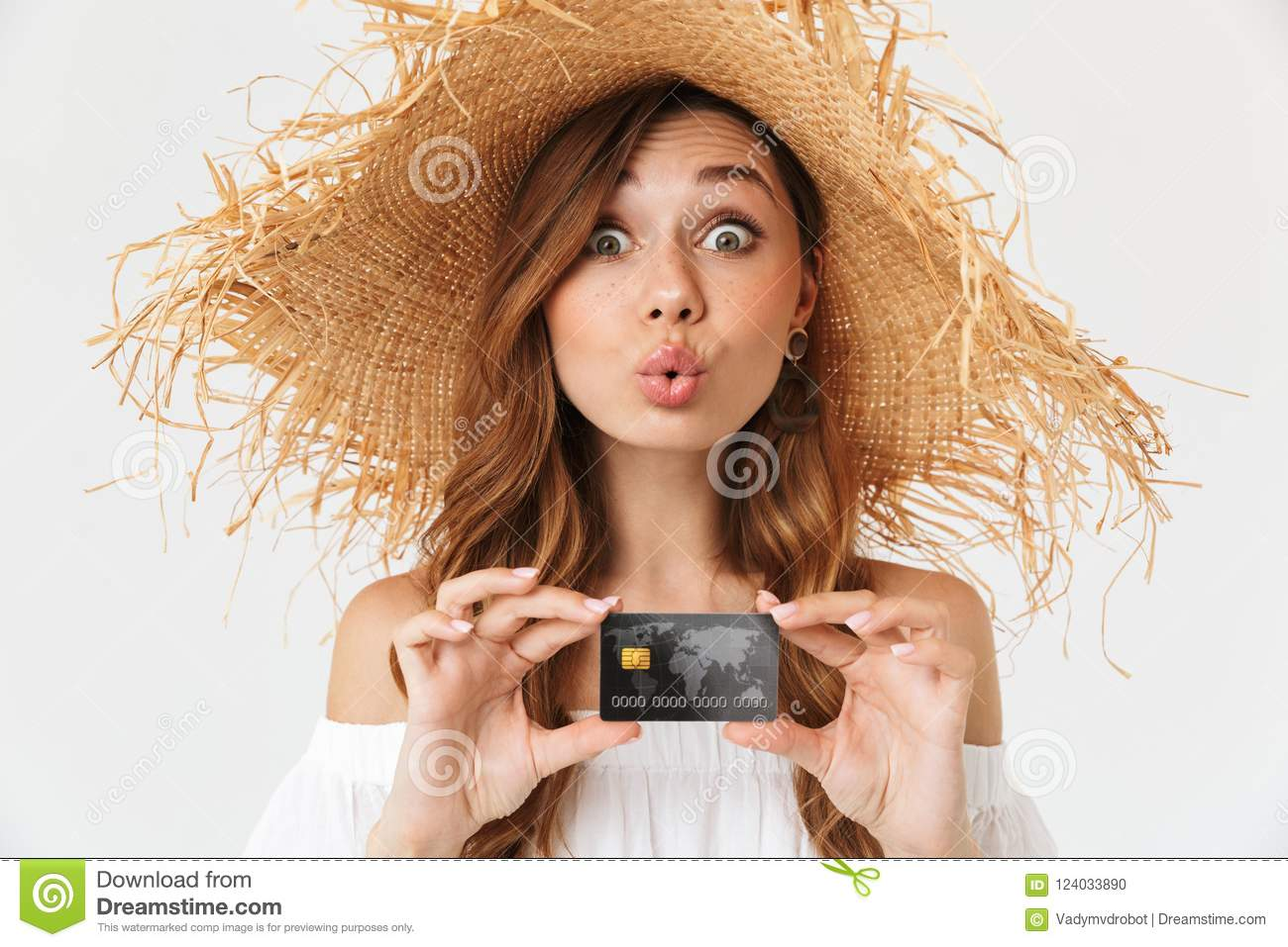 Portrait of cheerful young woman 20s wearing big straw hat rejoicing while holding credit card, isolated over white background