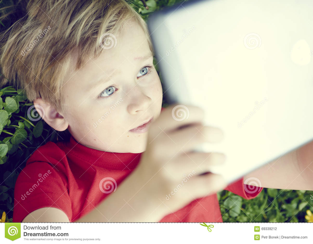 Portrait of child blond young boy playing with a digital tablet computer outdoors lying on grass listening music or watching movie facial expression
