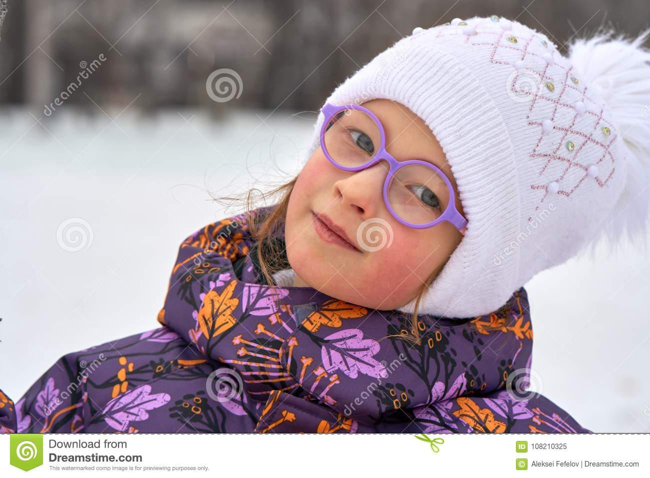 9264704d7 Portrait Of A Child Girl In Glasses On A Winter Walk. The Girl Is ...