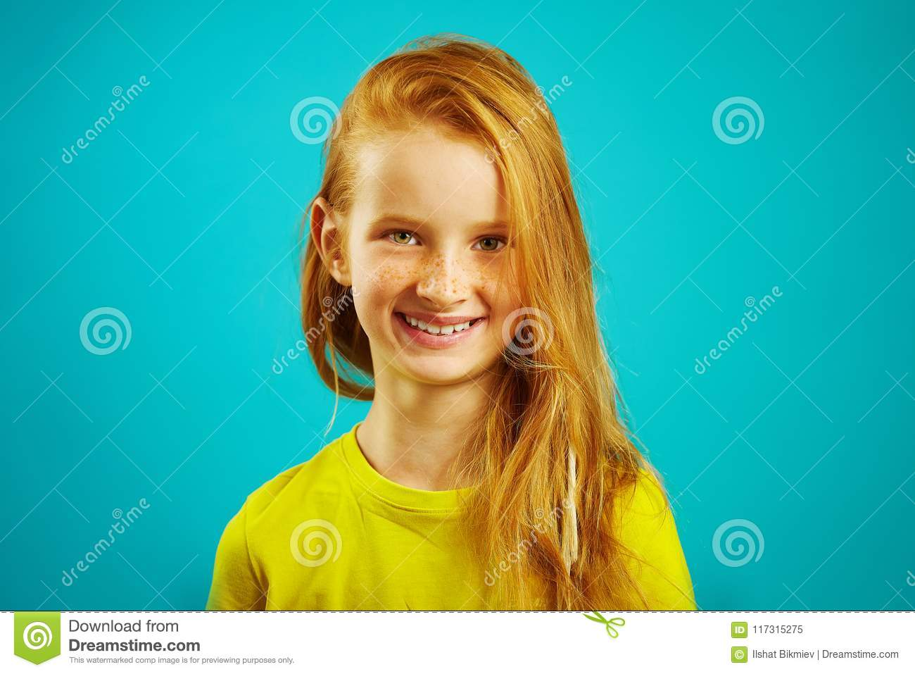 Portrait of children girl with cute smile, has red hair and beautiful freckles, dressed in bright t-shirt, child shot on