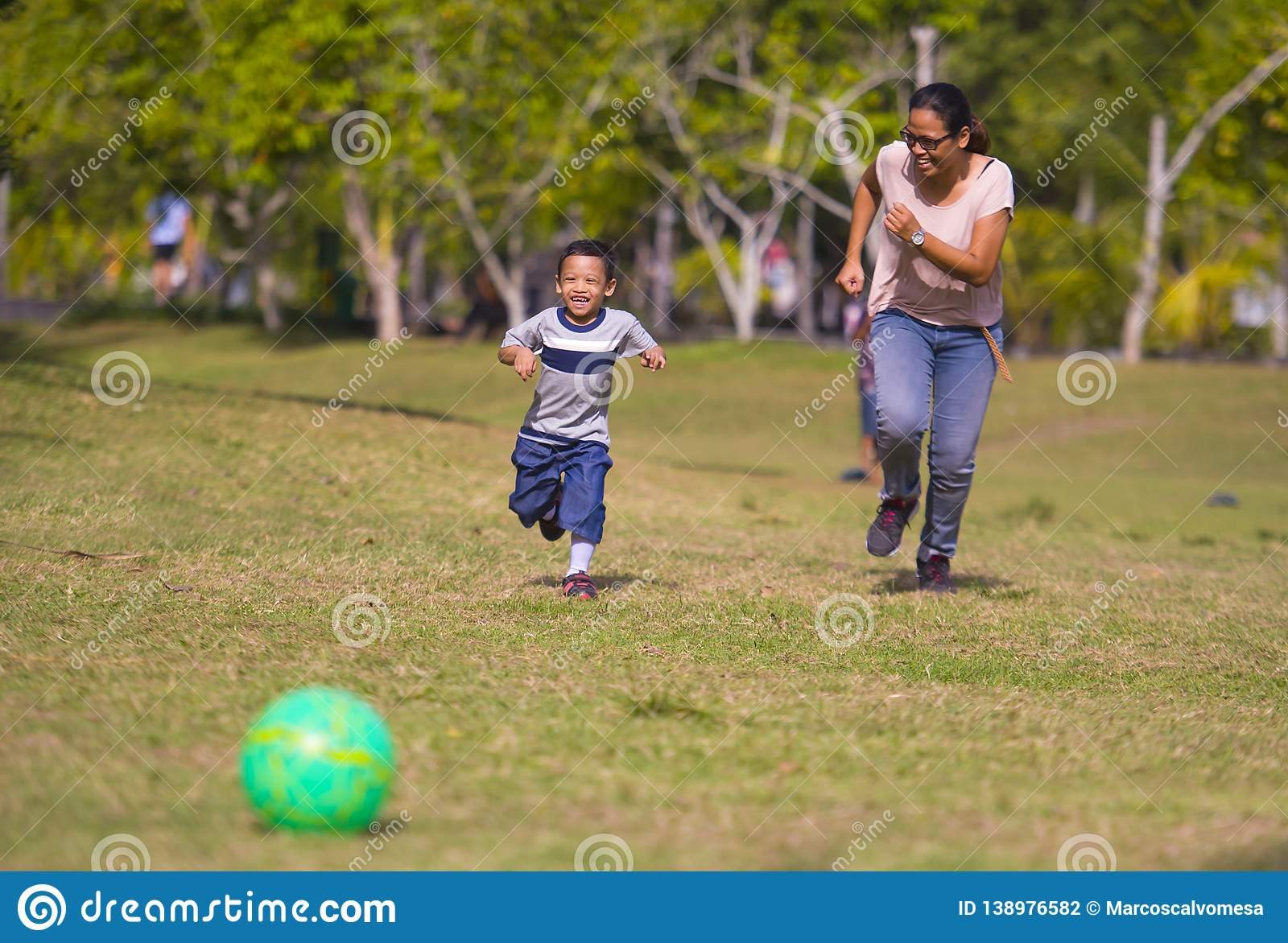 Happy Asian Indonesian mother playing football with little 5 years old son running together excited laughing having fun in soccer. Portrait in city park of happy stock photography
