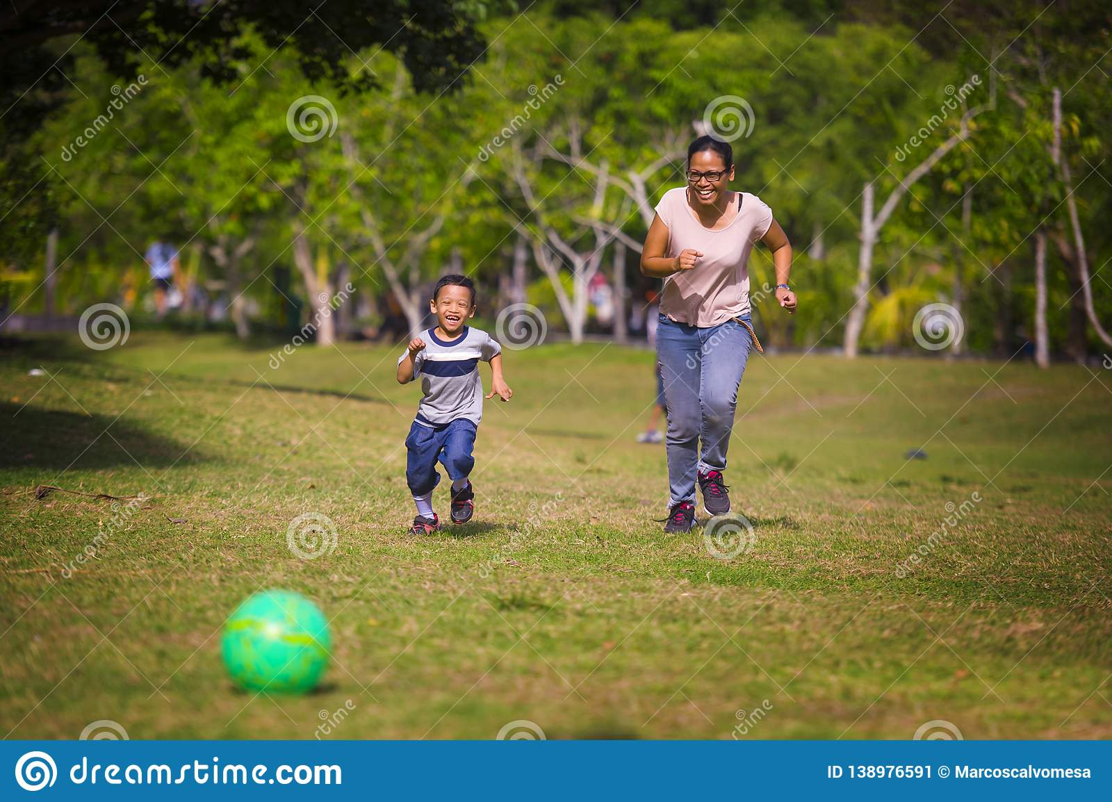 Happy Asian Indonesian mother playing football with little 5 years old son running together excited laughing having fun in soccer. Portrait in city park of happy stock image