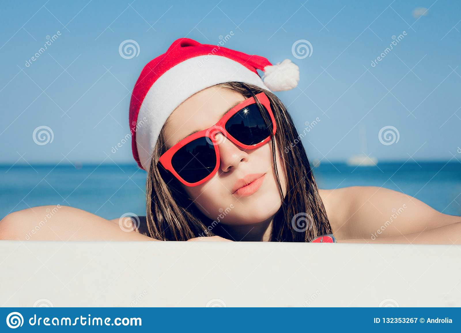 Portrait close up of a pretty teenage girl in Santa Claus hat