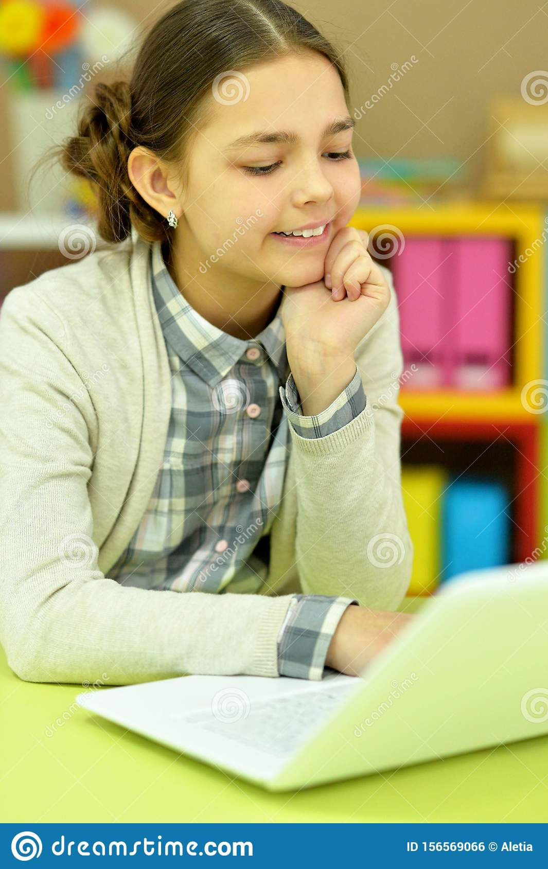 Portrait of concentrated little girl with laptop studying