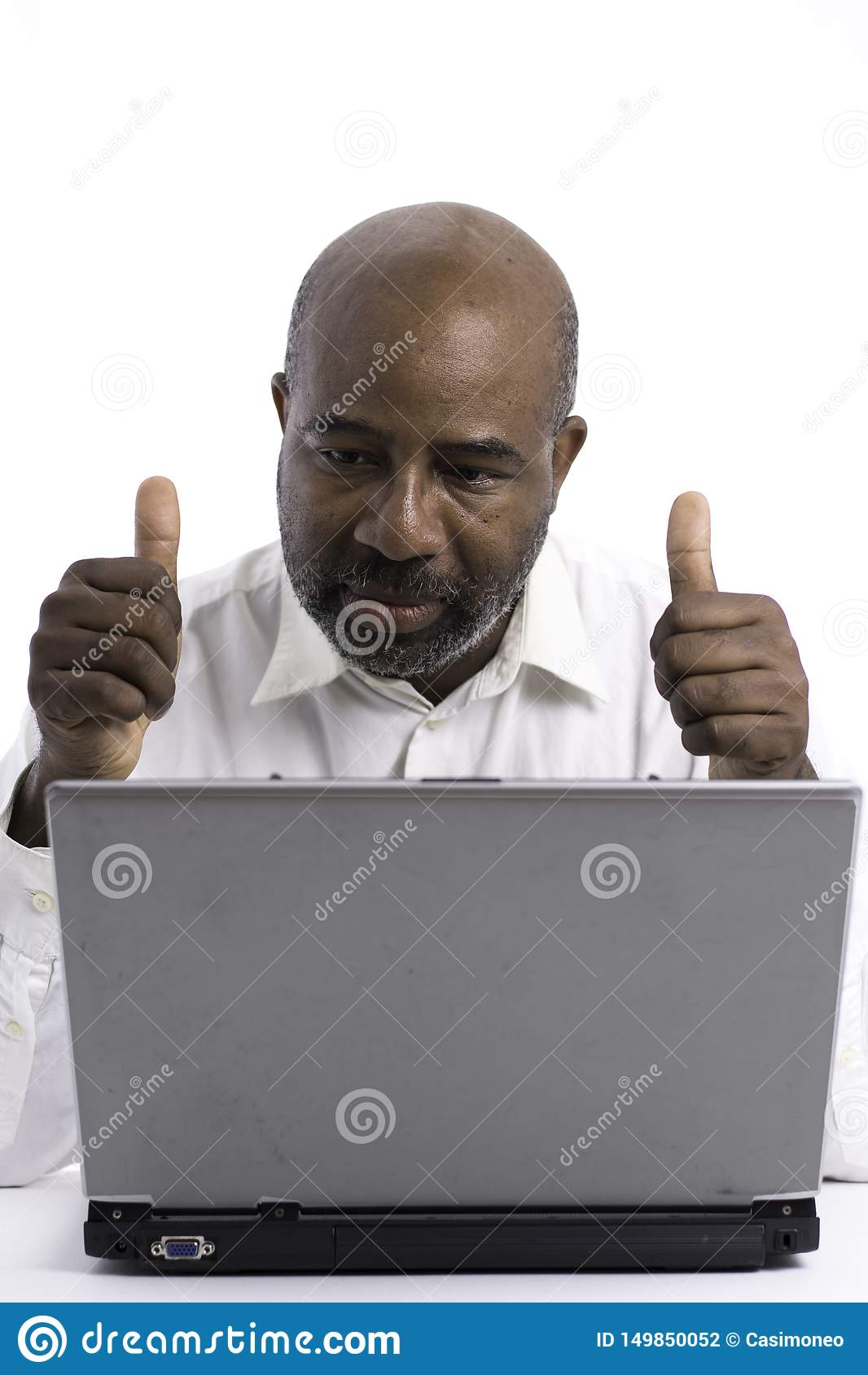 Portrait of a confident African American software expert signaling ok with thumbs up while sitting front of a laptop computer.