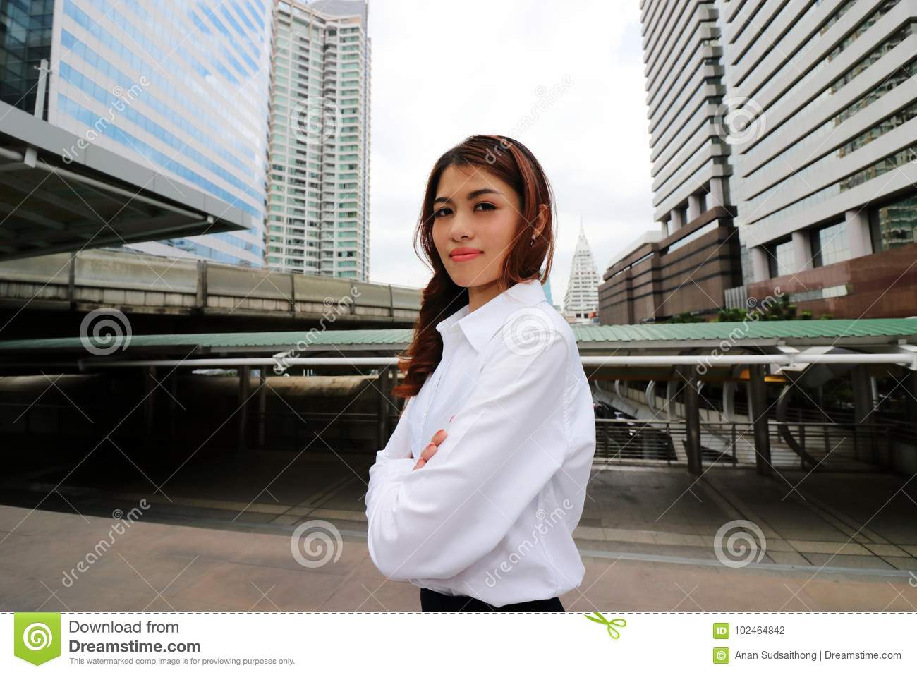 Portrait of confident Asian businesswoman standing and looking at camera against urban building city background. Leader woman busi