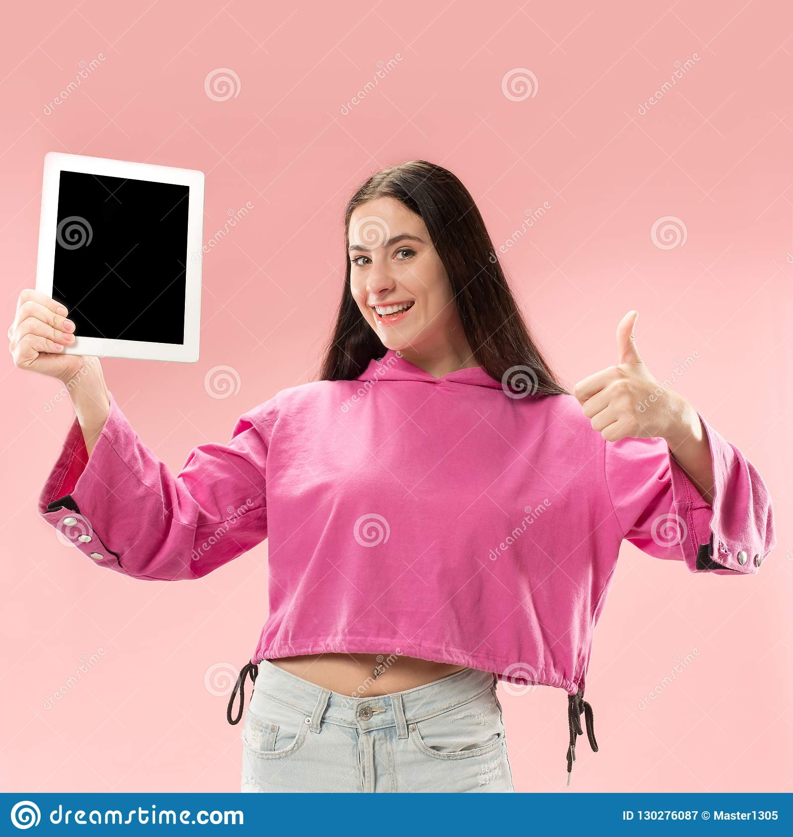 Portrait of a confident casual girl showing blank screen of laptop over pink background