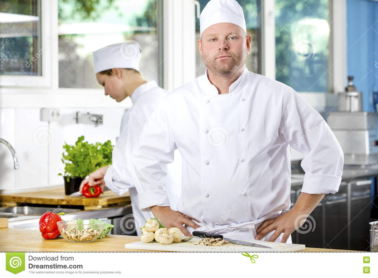 Portrait of confident chef making food in large kitchen