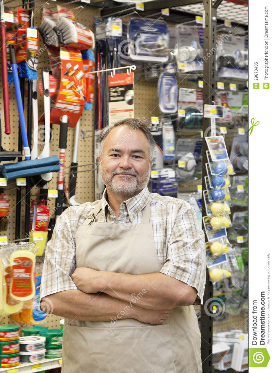 portrait of a confident mature store clerk with arms