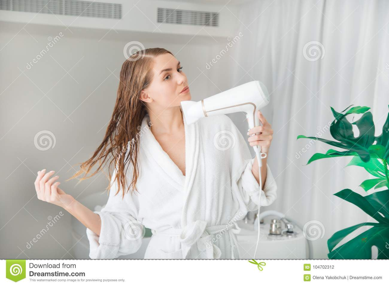 Portrait of confident young woman blow-drying her hair in bathroom. She is  standing in bathrobe b44260bcf
