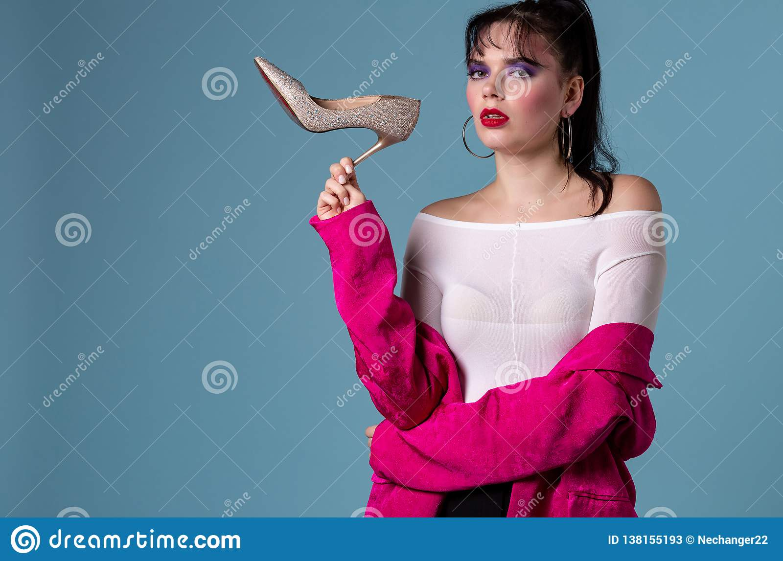 Portrait of a confused pretty woman in pink jacket holding high heels shoe
