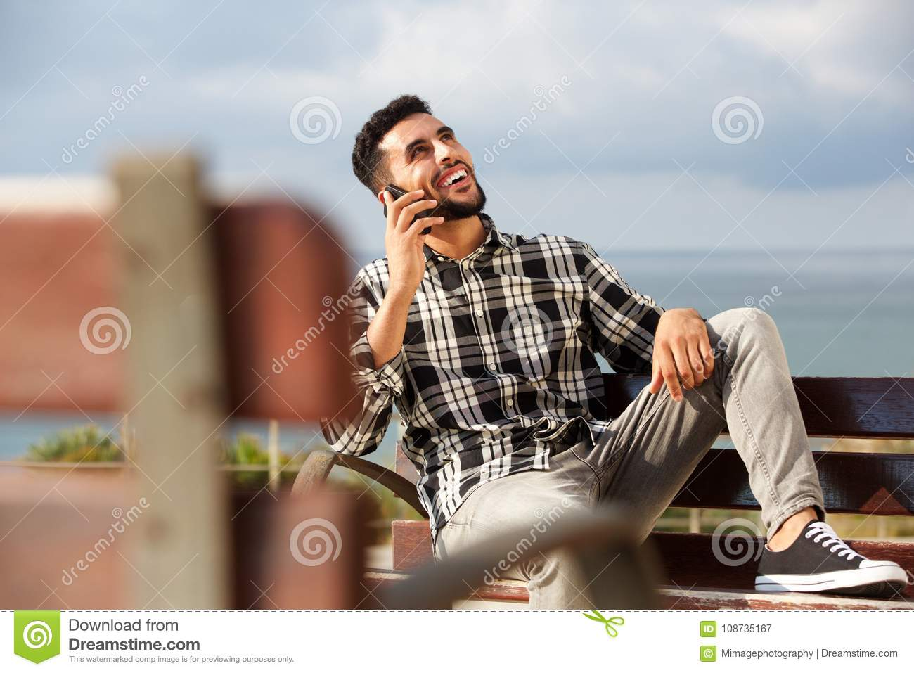 Cool young arabic man talking on mobile phone outdoors