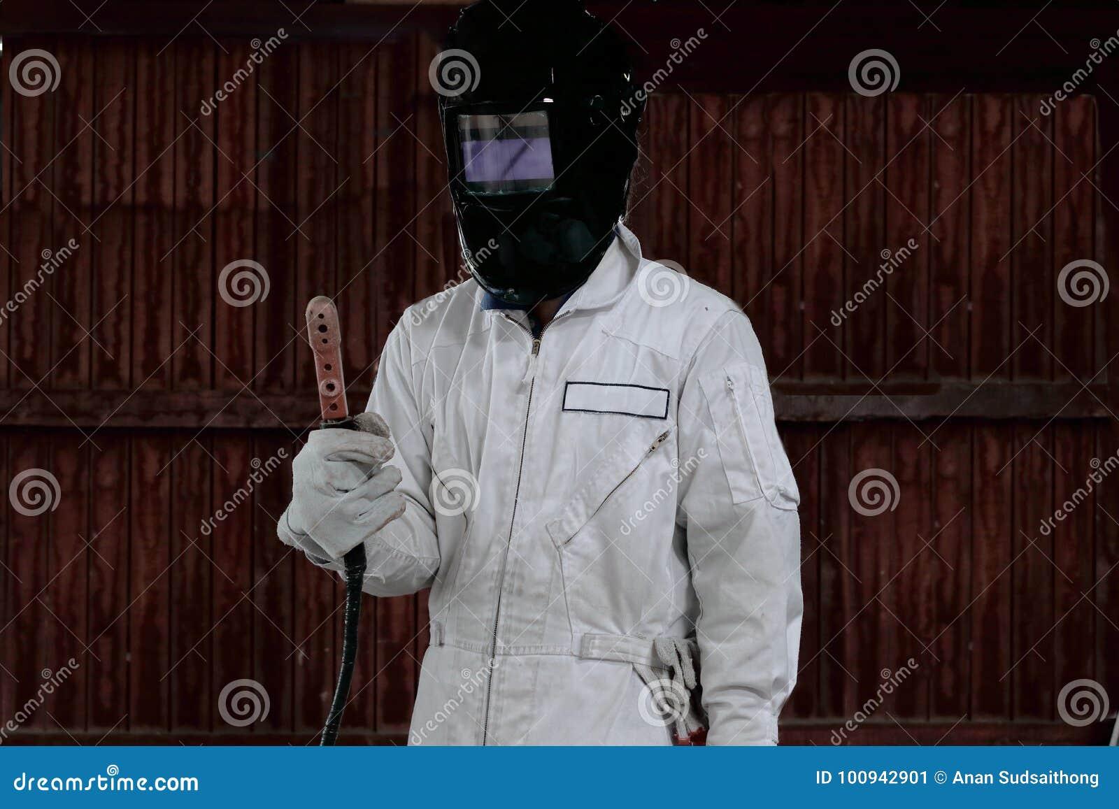 Portrait of craftsman welder in white uniform holding arc welding torch in hands. Industrial worker concept.