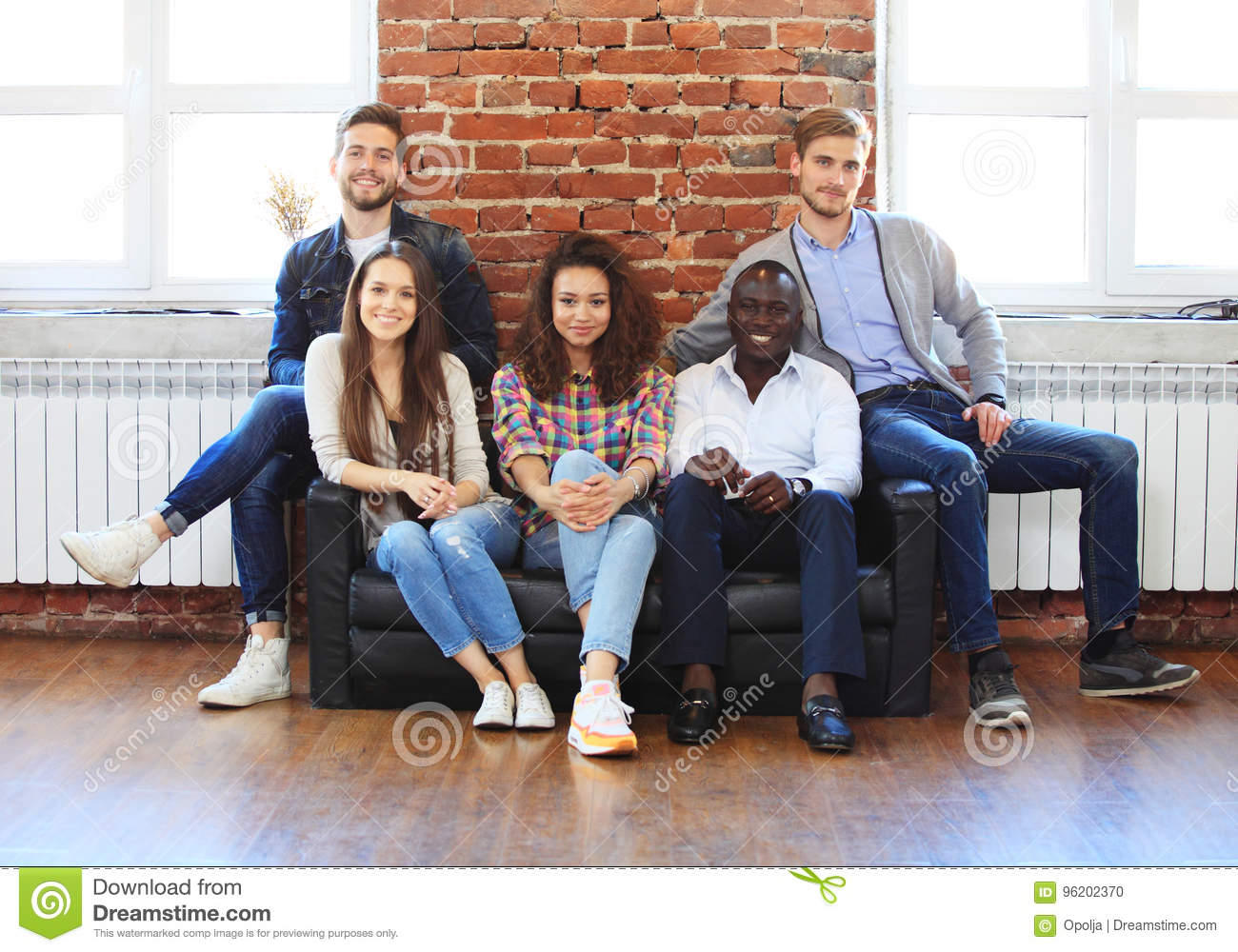 Portrait of creative business team sitting together and laughing. Multiracial business people together at startup.