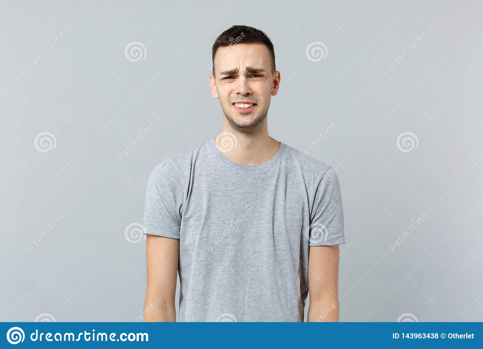 Portrait of crying upset dissatisfied young man in casual clothes standing, looking camera isolated on grey wall