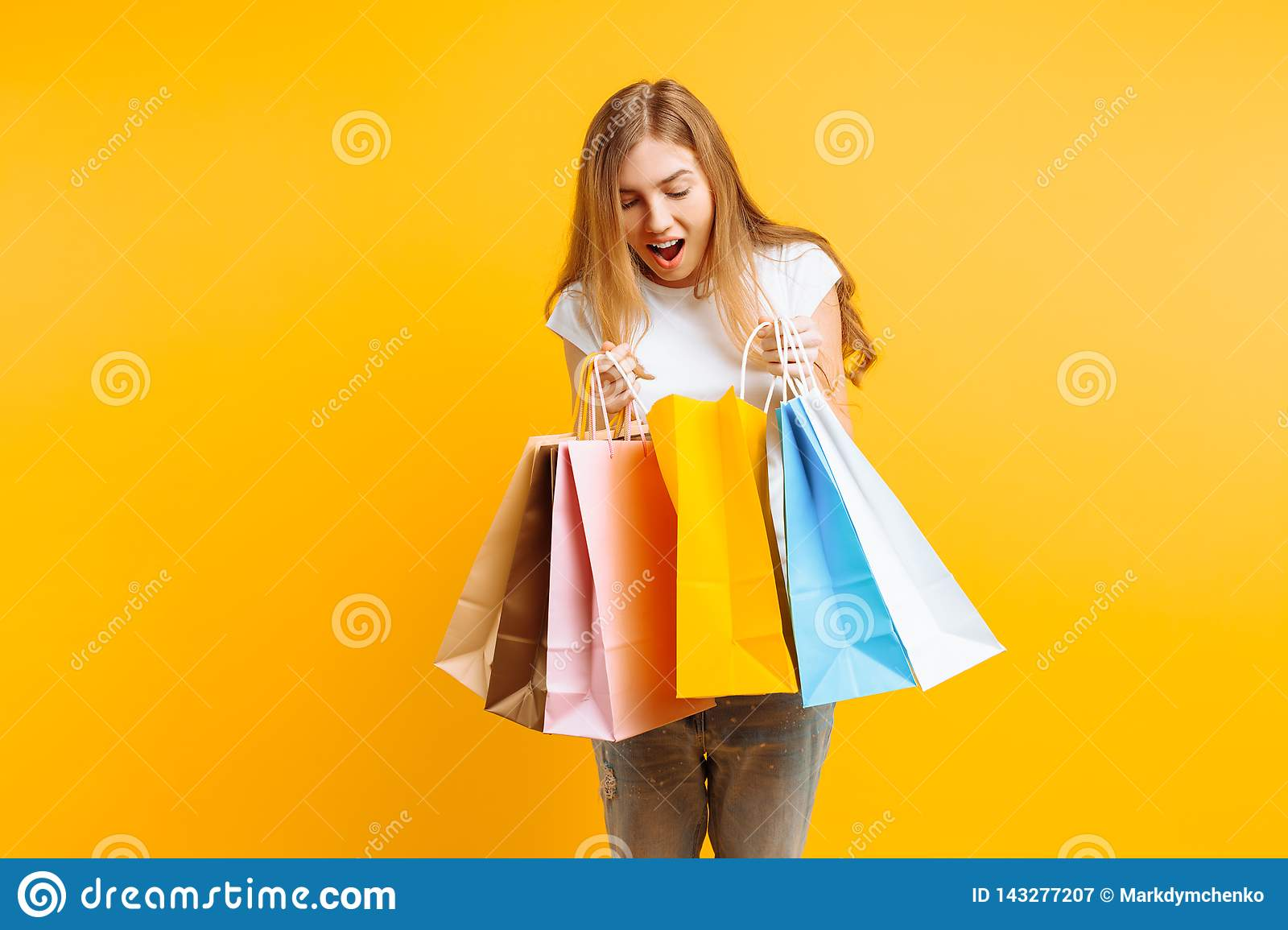 Portrait of a curious young woman , after a good shopping, looking inside the bag, isolated on a yellow background