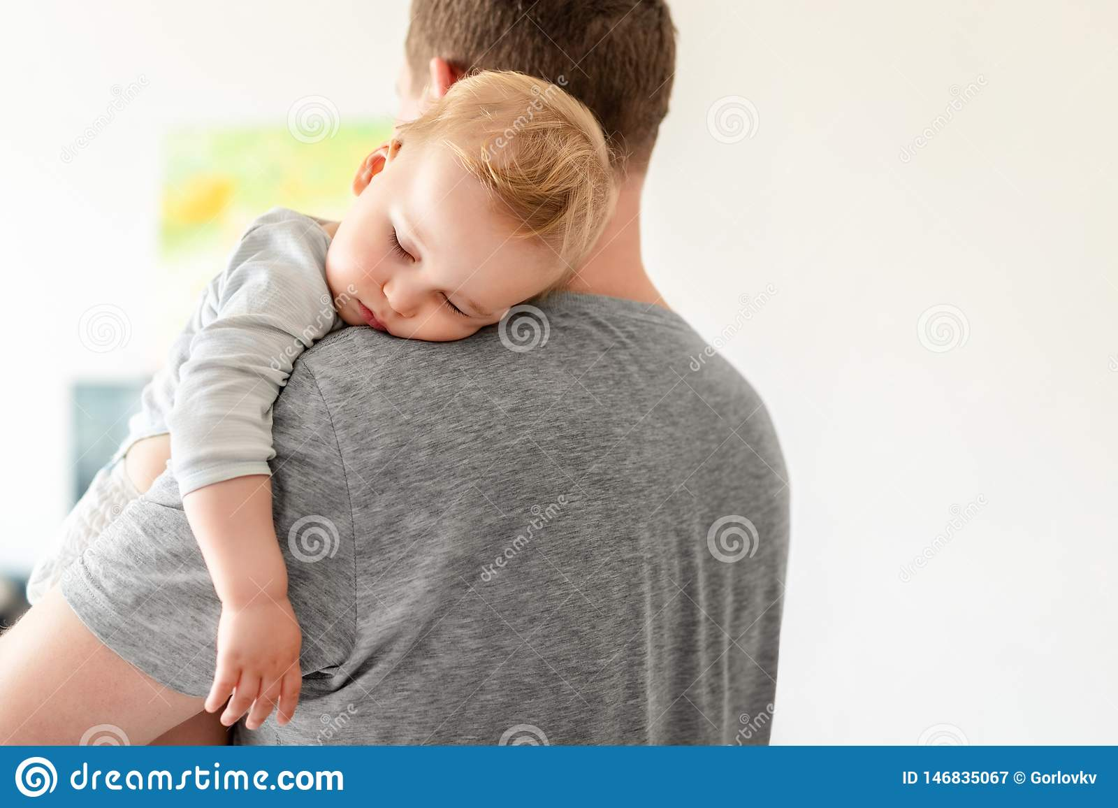 Portrait of cute adorable blond caucasian toddler boy sleeping on fathers shoulder indoors. Sweet little child feeling safety and