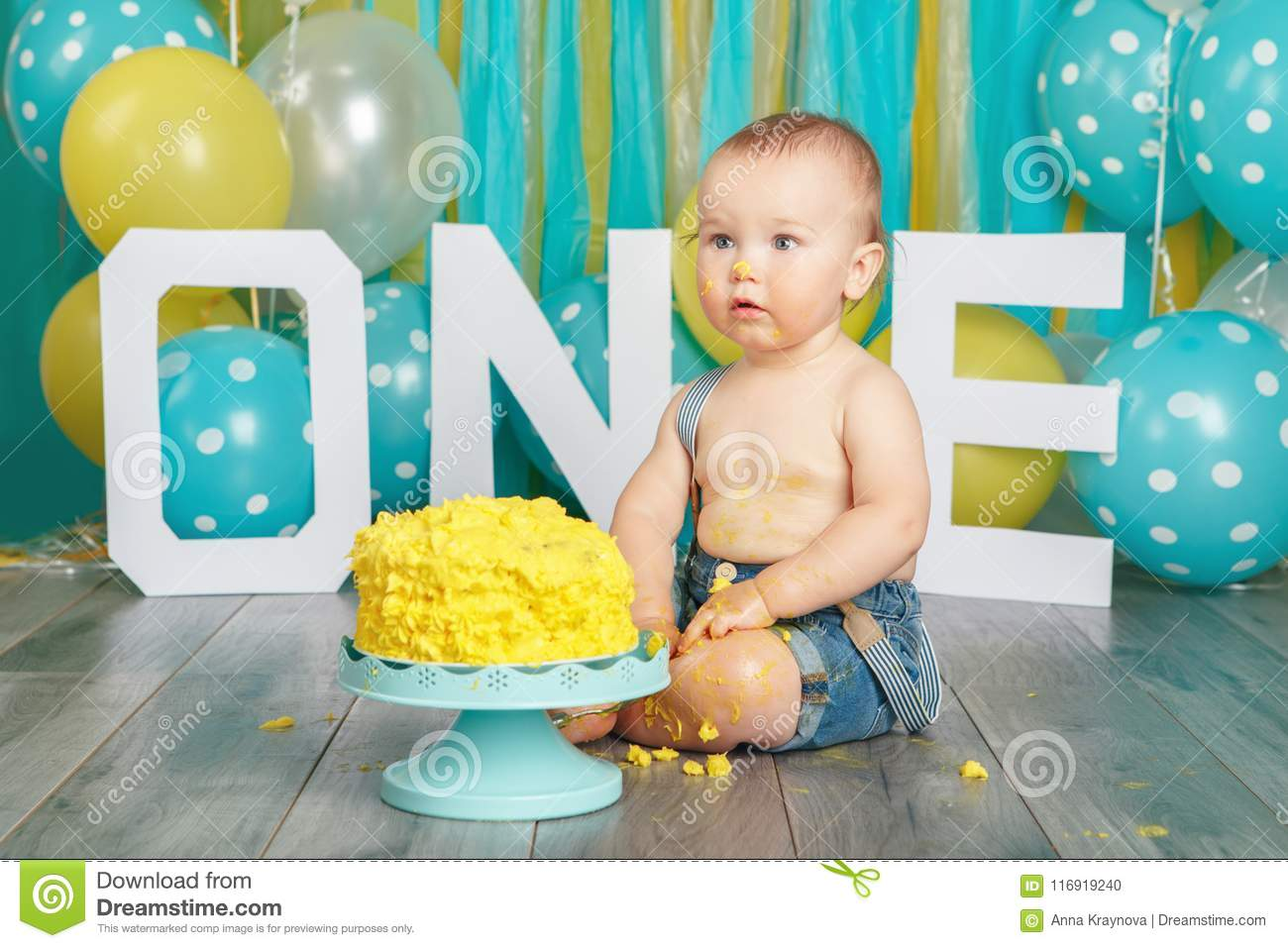 Portrait Of Cute Adorable Caucasian Baby Boy In Jeans Pants Celebrating His First Birthday Cake Smash Concept Child Kid Sitting On Floor Studio Eating