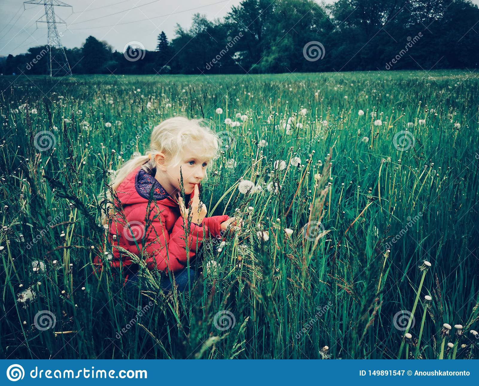 Caucasian girl walking among dandelions and grass on meadow at evening
