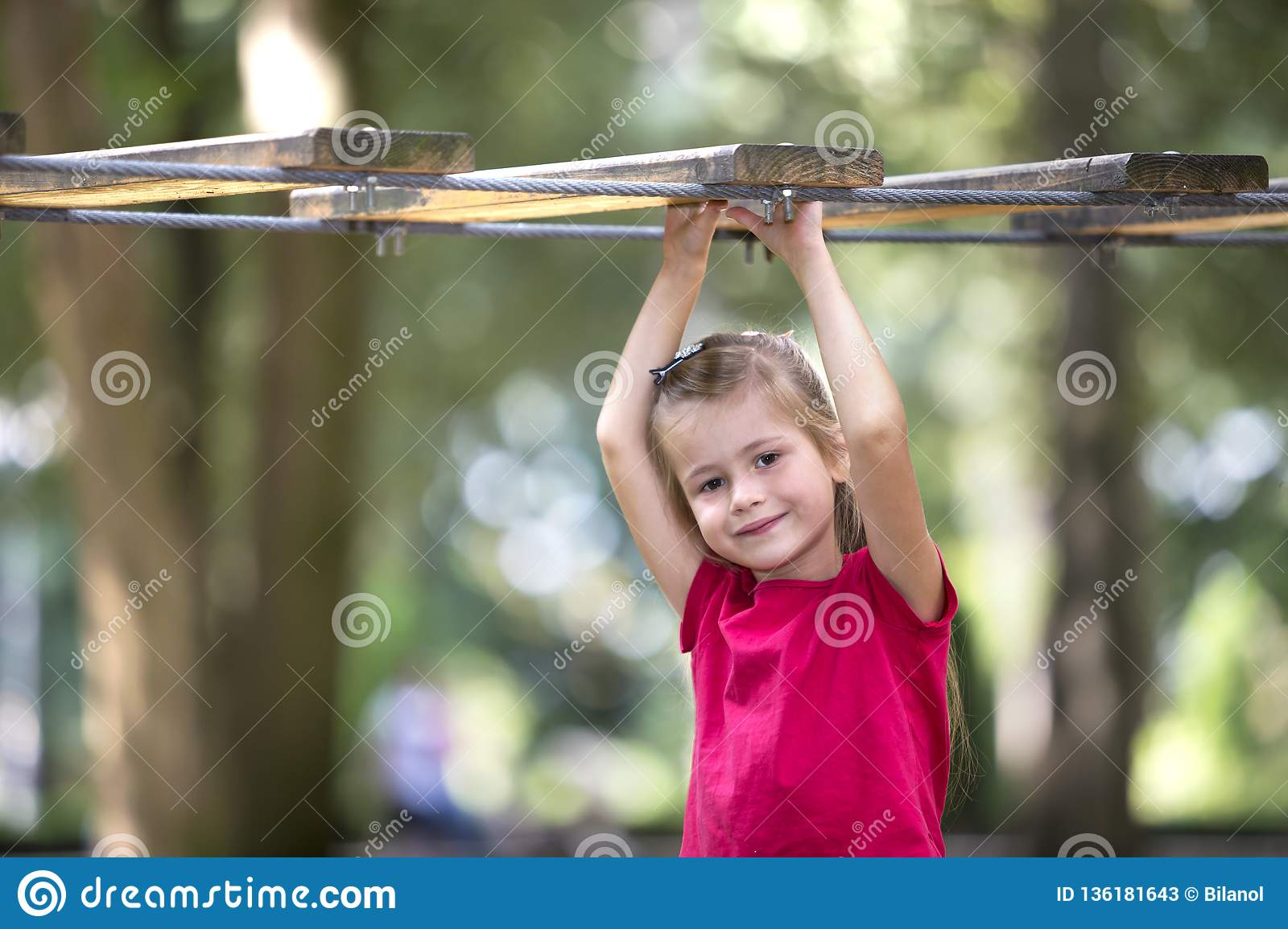 Portrait of cute adorable smiling blond child girl in summer pink dress with raised arms holding to rope way on blurred green