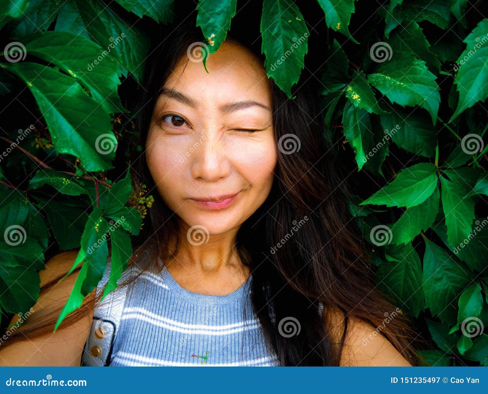 Portrait of a cute asian girl taking selfie on a green grape leaf background.